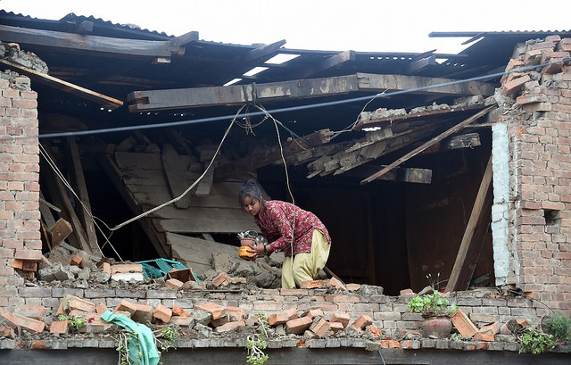 A Nepalese girl takes her belongings from her damaged house, Bhaktapur, Nepal  scrolleditorial/flickr